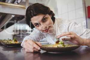 Female chef examining appetizer plate at order station