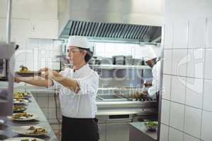 Female chef keeping appetizer plate ready on the order station