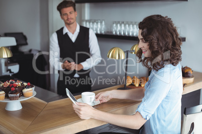 Customer using digital tablet while having coffee at counter