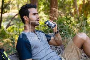 Man using binoculars while resting in the forest