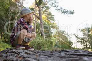 Boy sitting on the fallen tree trunk