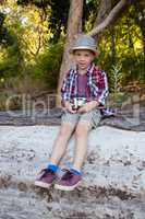 Boy sitting on the fallen tree trunk in the forest