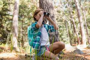 Girl looking through binoculars in the forest