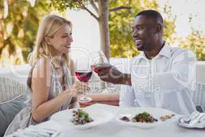 Romantic couple toasting their wine glasses