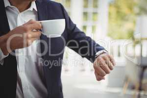 Mid section of businessman checking time while having coffee