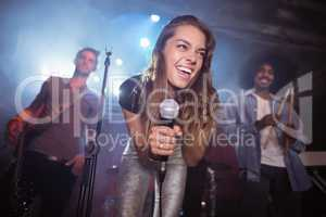 Cheerful young woman with musicians performing at nightclub