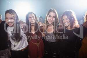 Portrait of young happy female friends at nightclub
