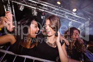Cheerful female friends enjoying at nightclub
