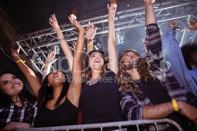 Low angle view of fans enjoying at music festival