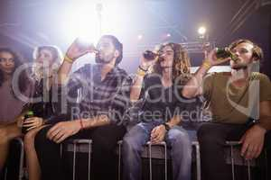 Male friends drinking beer at nightclub