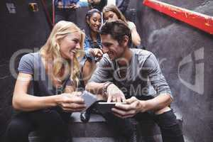 Cheerful friends using mobile phones on steps at nightclub