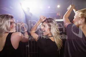 Happy female friends dancing at nightclub
