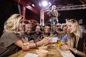 Woman showing smart phone to friends while sitting at table