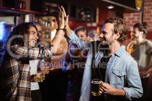 Friends doing high five in club