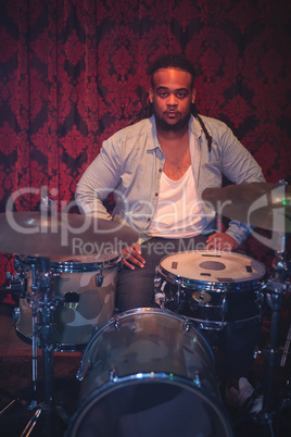 Portrait of musician sitting by drum kit