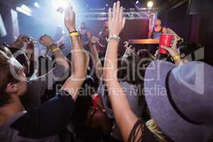 People with arms raised at nightclub
