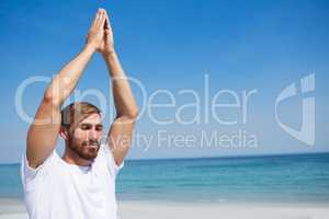 Man with hands clasped exercising at beach