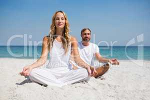 Full length of smiling couple exercising at beach