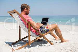Full length of man using laptop at beach