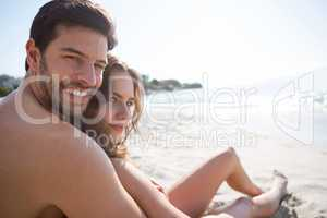 Portrait of young shirtless man with his girlfriend sitting at beach