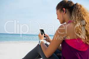 Young woman using mobile phone at beach