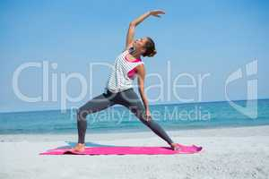 Full length of young woman exercising on mat at beach