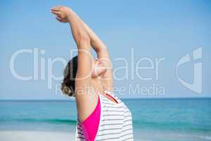 Young woman practicing yoga with arms raised at beach