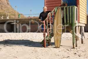 Man with surfboard standing on steps on beach hut