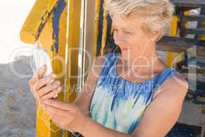 Close up of smiling senior woman listening music on smart phone