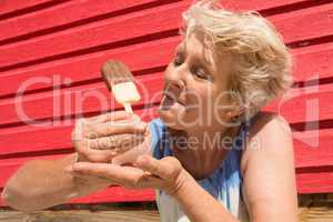Senior woman eating ice cream while standing by hut