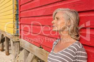 Close up of senior woman with eyes closed standing by wall