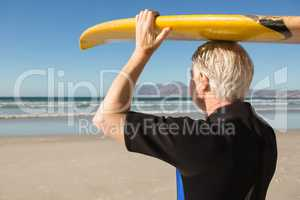Senior man carrying surfboard on head at beach