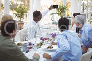 Group of friends taking selfie on mobile phone during lunch