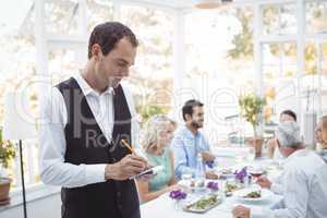 Smiling waiter writing order on notepad