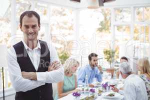 Smiling waiter standing with arms crossed while friends dining in background
