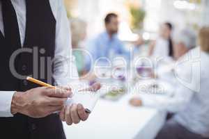 Waiter writing order on notepad