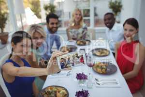 Friends taking selfie on mobile phone while having meal
