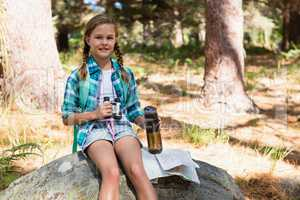 Girl with water bottle and binoculars sitting on the rock in forest