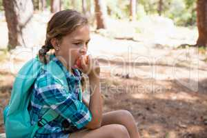 Girl having apple in the forest