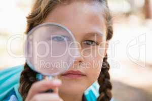 Girl looking through magnifying glass in the forest