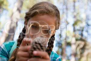Girl looking at dry pine cone through magnifying glass