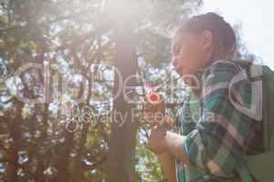 Girl blowing bubbles in the forest on a sunny day
