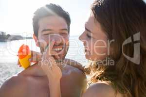 Happy young woman applying sunscream on man nose at beach