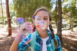 Girl blowing bubbles in the forest