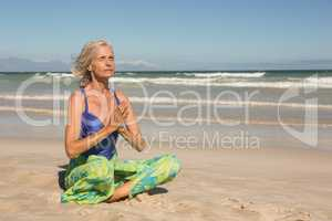 Close up of woman meditating while sitting on shore