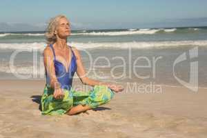 Close up of senior woman meditating while sitting on shore