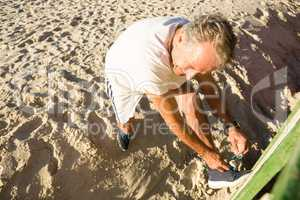 High angle view of man tying shoelace while standing on sand