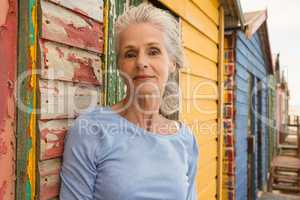 Portrait of confident senior woman standing by wall