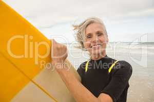 Close up of smiling senior woman holding surfboard while standing on shore