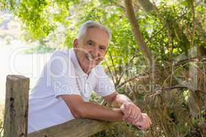 Portrait of smiling senior man leaning on wooden fence